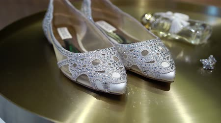 серьги : Bridal wedding shoes with pastes and jewelry earrings on golden background steadicam Стоковые видеозаписи