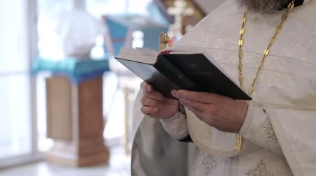 ksiądz : Priest praying with Bible book in church at ceremony Wideo