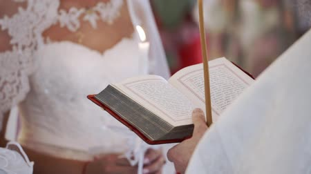 Priest praying with Bible book in church at wedding ceremony