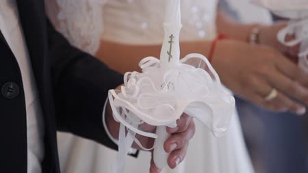 Bride and groom holding candles in church at christianity wedding ceremony Stock mozgókép