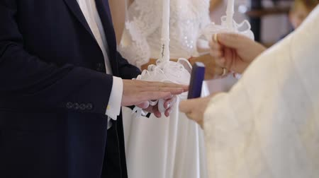 paus : Priest praying in church at wedding ceremony and put on rings for newlyweds bride and groom