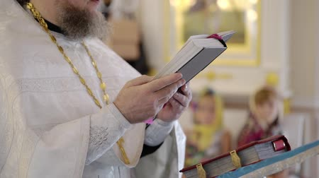 Priest praying with Bible book in church at ceremony Stock mozgókép