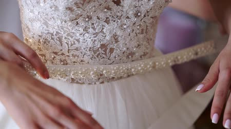 Young woman wearing bridal dress at wedding day and put on belt