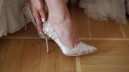 Bride wearing bridal wedding shoes sitting on bed Stock mozgókép