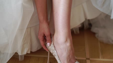 pastas : Bride wearing bridal wedding shoes sitting on bed Stock Footage