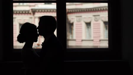 Silhouette of lovely couple kissing and embracing in a city near window
