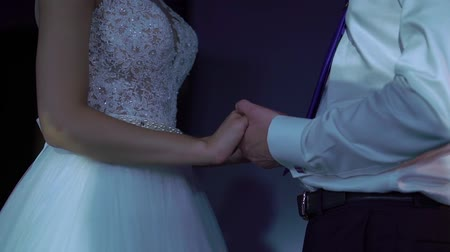 Bride and groom holding hands at the party indoors