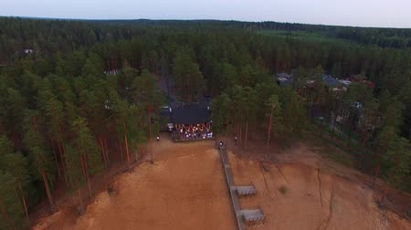 коттедж : Countryside cottage on a beach near lake at the evening celebration outdoors. People have fun and dancing on a deck with garlands. Aerial drone shot.
