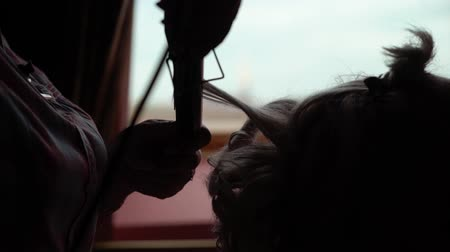 curling hair : Hair stylist making curls on customer hair using electric curler or curling iron indoors near window at home Stock Footage