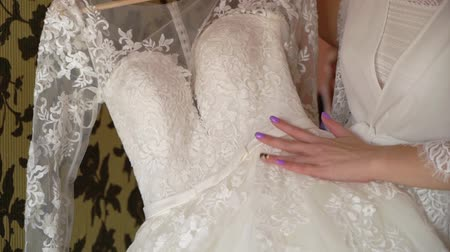 negligee : Bride morning preparation. Beautiful bride in white wedding negligee holding wedding dress. Tender moment of women best day in bedroom.