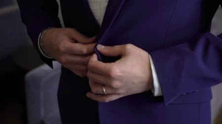 smokin : Close-up view of the hands of the groom or businessman buttoning the wedding jacket.