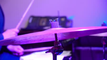 bas : Man plays musical percussion instrument with sticks closeup on a concert stage, a musical concept with the working drum close up
