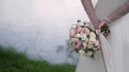 casar : Bride holding her bouquet behind her back. Staying near pond, lake or river. Vídeos
