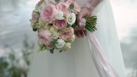 wed : Bride holding her bouquet behind her back. Staying near pond, lake or river. Stock Footage