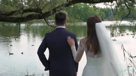 comes : Bride in splendid wedding dress coming to handsome groom and hugging each other. Rear view, lake or pond on background.