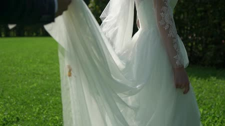 házasodik : Bride and groom walking across park at sunny summer day. Holding hands, slowmotion