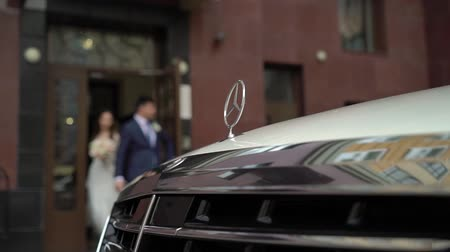 só : SAINT-PETERSBURG, RUSSIA - SEPTEMBER 9, 2018: White business class luxury Mercedes car, bride and groom on background unrecognizable near house yard Stock Footage