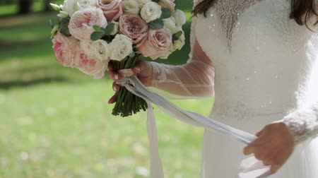 cüppe : Wedding bouquet in brides hands. Woman staying in park at sunny day holding flowers in hand and waving ribbons.