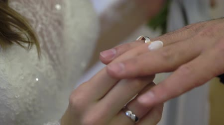 him : Bride putting a wedding ring on grooms finger indoors closeup