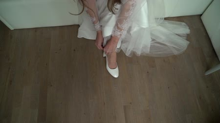 casar : Bride puts on her wedding white shoes on high heels sitting in bedroom