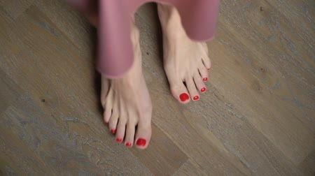 ポーランド語 : Womens legs with red pedicure. Womens feet staying and going barefoot on the floor at home. 動画素材