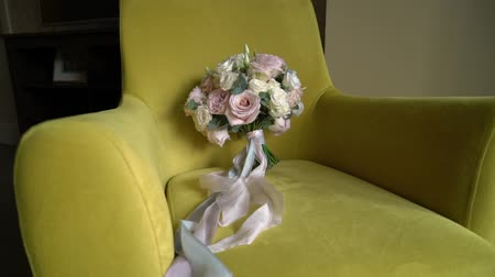 cadeiras : Wedding bridal bouquet of pink and white roses lying on yellow chair Stock Footage