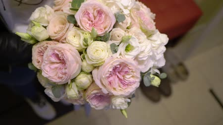 virágárus : Wedding bridal bouquet of pink and white roses. Woman florist holding flowers. Stock mozgókép