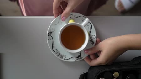 латте : Woman holding hot cup of tea. White mug, drinking hot tea or coffee. White table with drink, top view Стоковые видеозаписи