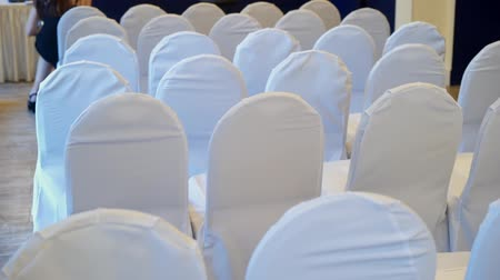 устроенный : Chair with white cover cloth back side in a row in a big hall for wedding, conference or seminar steadicam