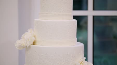 elegant dessert : Four tiered white celebration wedding cake in restaurant