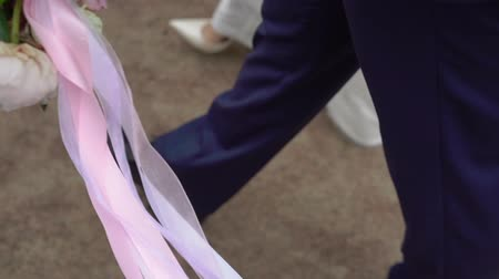 casar : Outdoor Bride and Groom holding flower bouquet with pink and white peonies and walking in park slowmotion