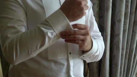 manşet : Businessman wearing cuff link, man putting and adjusting cufflink at white shirt, groom getting ready in the morning before wedding ceremony indoors Stok Video
