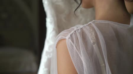 negligee : Rear view of bride in lingerie in the morning before the wedding. White negligee of the bride, preparing for the wedding ceremony. Girl holding her white dress in bedroom