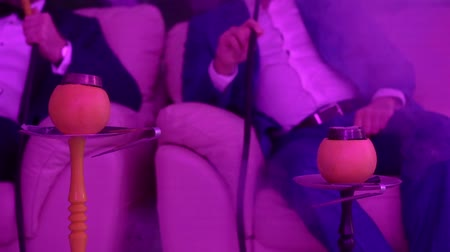 loungebar : Hookah on orange fruit. People smoking shisha at the party. Man sitting on sofa in nightclub and smoking