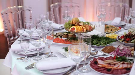 beige stof : Tables set for an event party or wedding reception. luxury elegant table setting dinner in a restaurant. glasses and dishes indoors Stockvideo