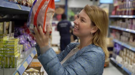 supermarket shelf : Woman shopping at the supermarket. Choosing food products in a shop Stock Footage