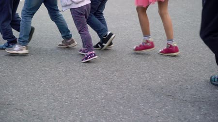 youngsters : Group of children running on a street outdoors. Unrecognizable child, legs only