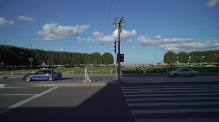 furnér : Young blonde woman smiling and posing in a city slowmotion at the summer evening. On a pedestrian zebra crossing waiting.