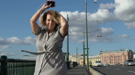 furnér : Young blonde woman smiling and posing in a city slowmotion at the summer evening at the bridge