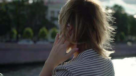 folheado : Young blonde woman smiling and posing in a city slowmotion at the summer evening at the bridge