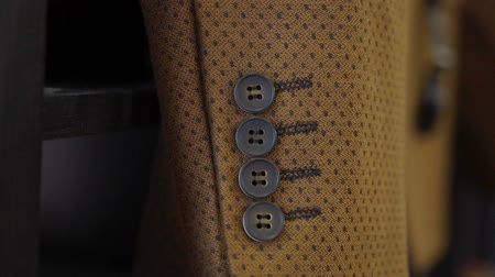 vestindo : Brown suit jacket sleeve with buttons closeup. Mans fashion clothes. Groom or wedding concept Vídeos