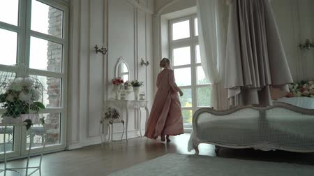 żyrandol : Young woman in pink boudoir dress circling and undressing. Preparing to put on wedding dress in bedroom Wideo