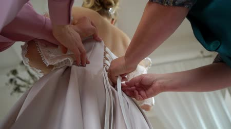 buttoning : Bride and her mother put on wedding dress. Bridesmaid helping to wear