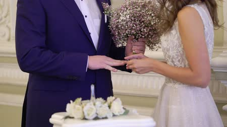 nowożeńcy : Bride and groom put on wedding rings at ceremony