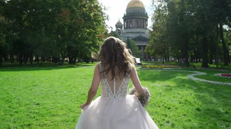st isaac's cathedral : Young brunette strong bride running in a park at sunny summer day. Wedding day. Stock Footage