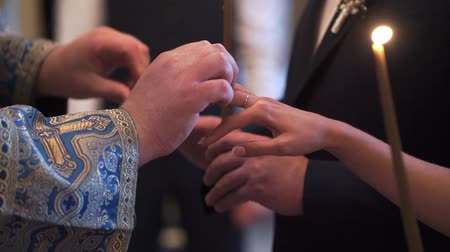 clergyman : Priest praying in church at wedding ceremony and put on rings for newlyweds bride and groom