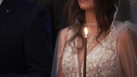 ksiądz : Bride and groom holding candles in church at christianity wedding ceremony Wideo