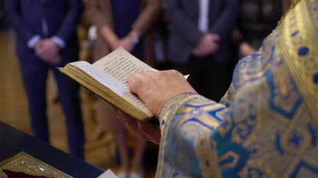 bibliai : Priest praying with Bible book in church at ceremony Stock mozgókép