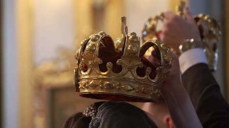 ksiądz : Crowns for wedding in church. Newlyweds at ceremony, priest praying