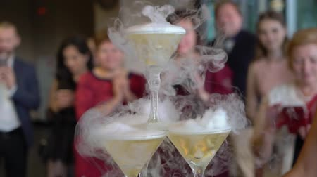 alkoholos : People taking drinks from pyramid tower of glasses with champagne. Pouring wine to tower of glasses